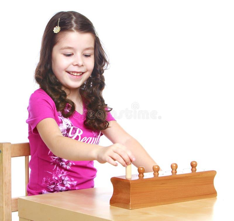 La niña oscuro-cabelluda en un Montessori fotos de archivo libres de regalías