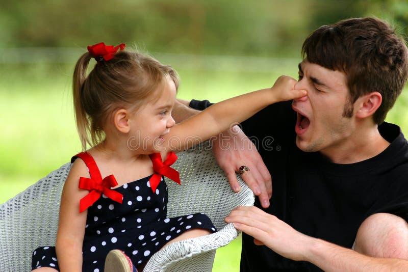 La niña pellizca la nariz imagen de archivo
