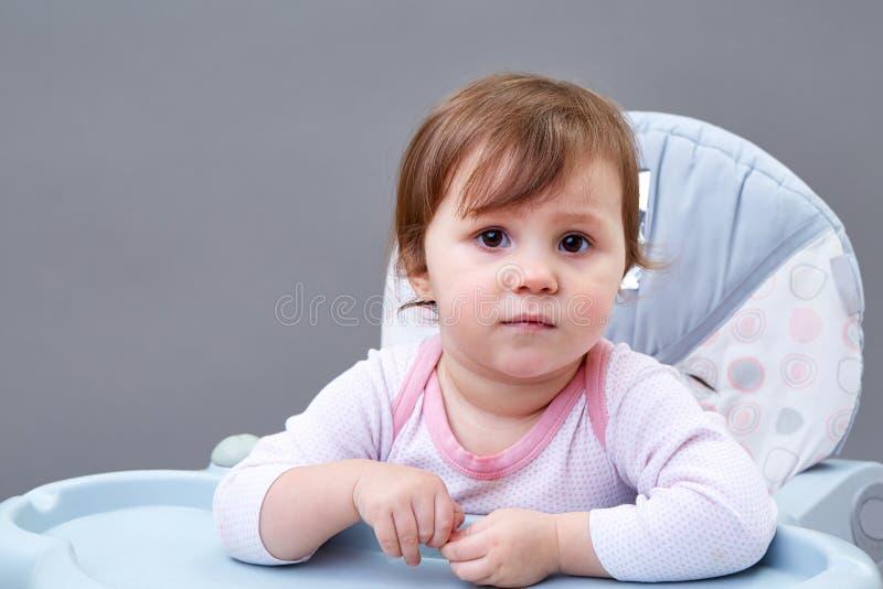 La niña pequeña adorable se está divirtiendo mientras que come algunas frutas en fondo grisáceo imagenes de archivo