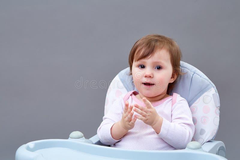 La niña pequeña adorable se está divirtiendo mientras que come algunas frutas en fondo grisáceo foto de archivo