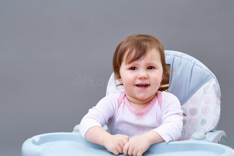 La niña pequeña adorable se está divirtiendo mientras que come en fondo grisáceo fotografía de archivo