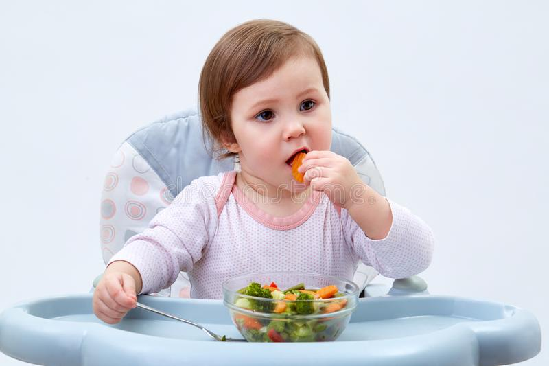 La niña pequeña adorable se está divirtiendo mientras que come verduras guisadas en el fondo blanco fotos de archivo