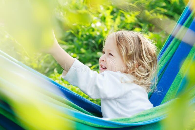 La niña pequeña de dos años es de risa y que juega en hamaca brasileña azulverde rayada fotos de archivo libres de regalías