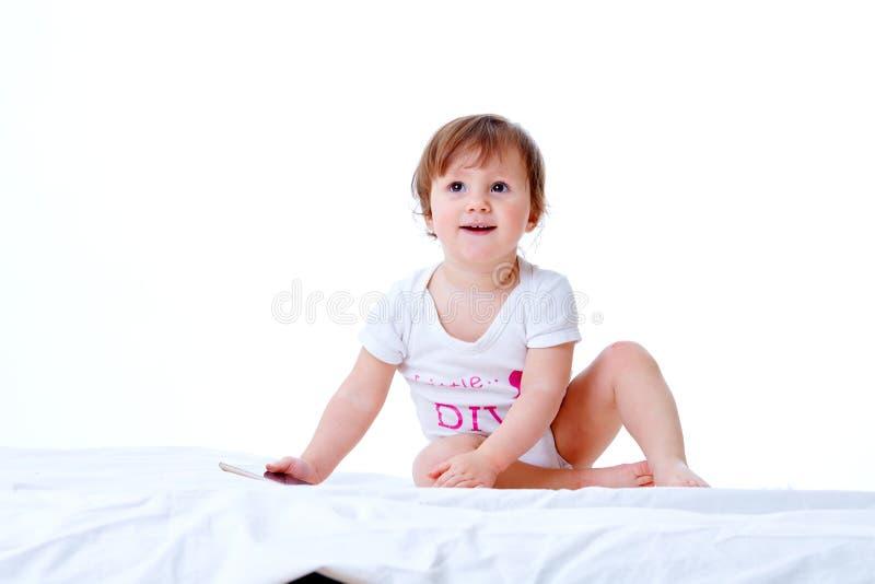 La niña pequeña linda se está divirtiendo mientras que come las pastas en el fondo blanco imágenes de archivo libres de regalías