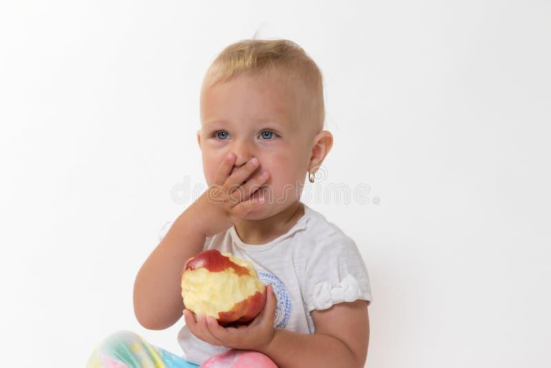 La niña pequeña que sostiene la manzana roja está cubriendo su boca con la mano fotos de archivo