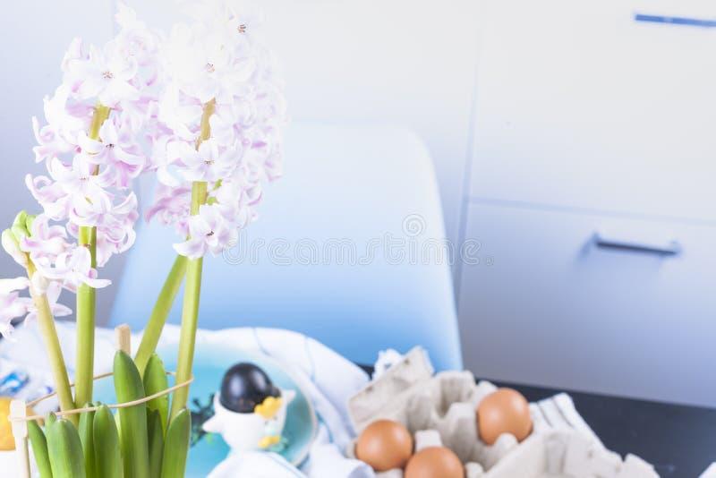 La niña pinta los huevos para Pascua en la cocina en casa Artículos del niño y del día de fiesta de la primavera Un niño feliz di fotografía de archivo