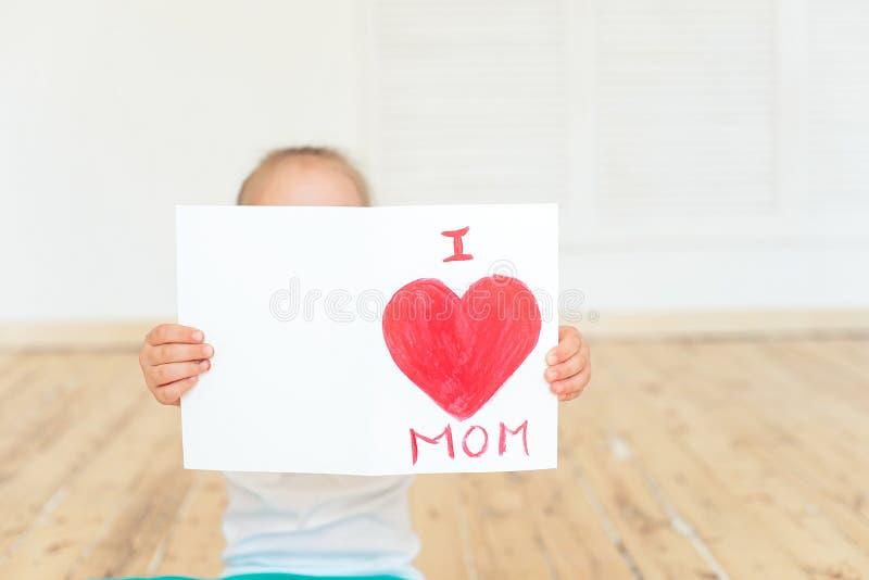 La niña pinta la tarjeta de felicitación para la mamá imagen de archivo