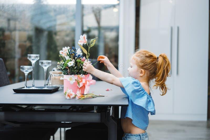 La niña pone las flores en la tabla fotos de archivo