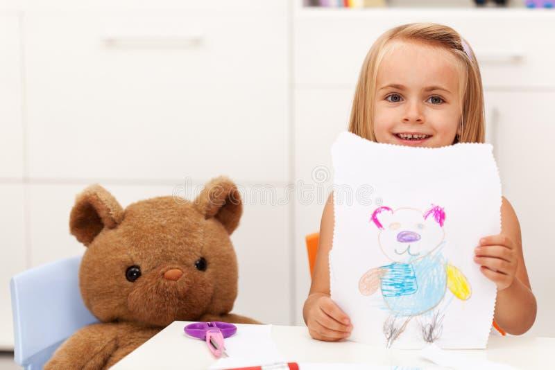 La niña presenta su dibujo - un retrato de su oso del juguete imagen de archivo
