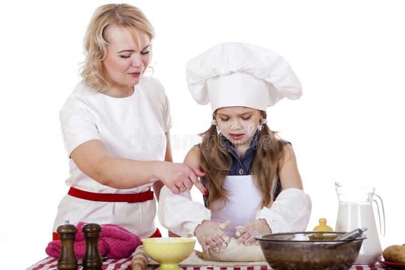 La niña que ayuda a su madre prepara una torta foto de archivo libre de regalías