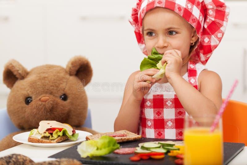 La niña que juega y que come un bocado sano con su peluche sea foto de archivo libre de regalías