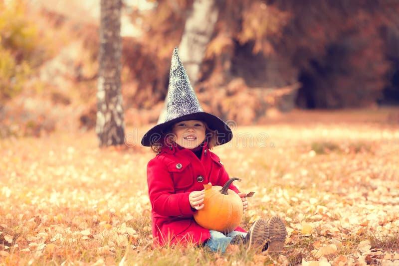 La niña que lleva el sombrero de la bruja de Halloween y calienta la capa roja, divirtiéndose en día del otoño imagen de archivo