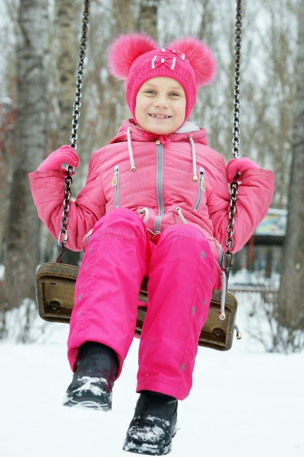 La niña que lleva la ropa brillante está balanceando en un oscilación al aire libre en invierno imagenes de archivo