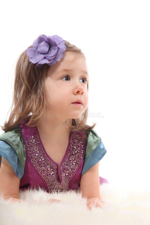 La niña que miente en la alfombra y mira para arriba fotos de archivo