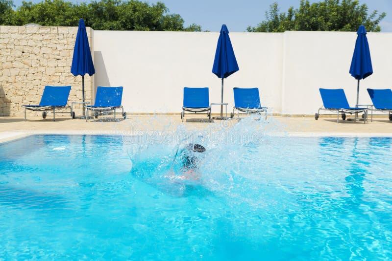 La niña que salta en bomba en una piscina al aire libre imágenes de archivo libres de regalías