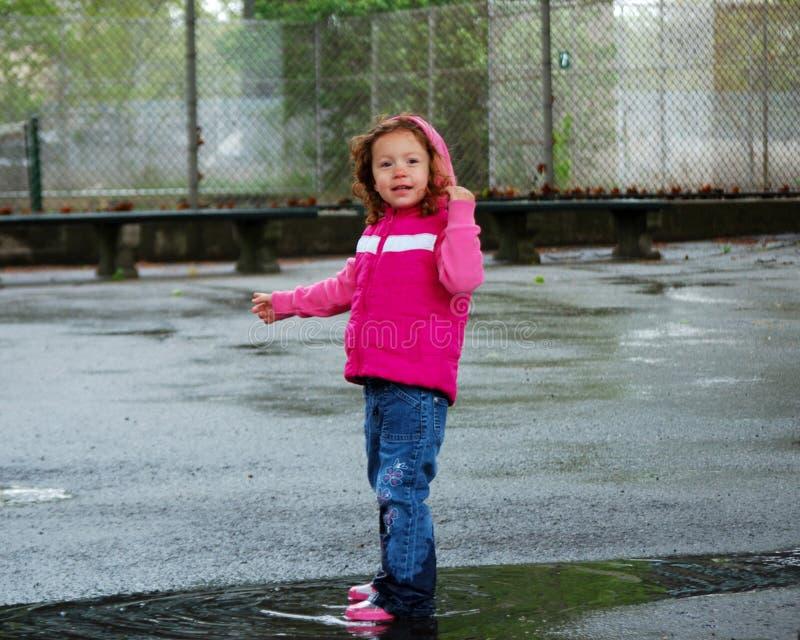 La niña que salta en charco fotografía de archivo