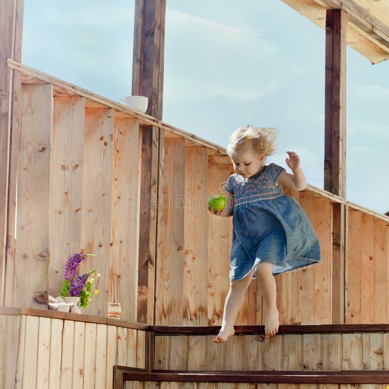 La niña que salta en las escaleras de una casa de campo fotografía de archivo