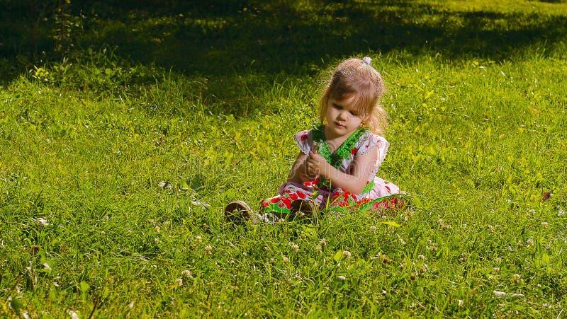 La niña que se sentaba en el césped se encendió por el sol imagen de archivo