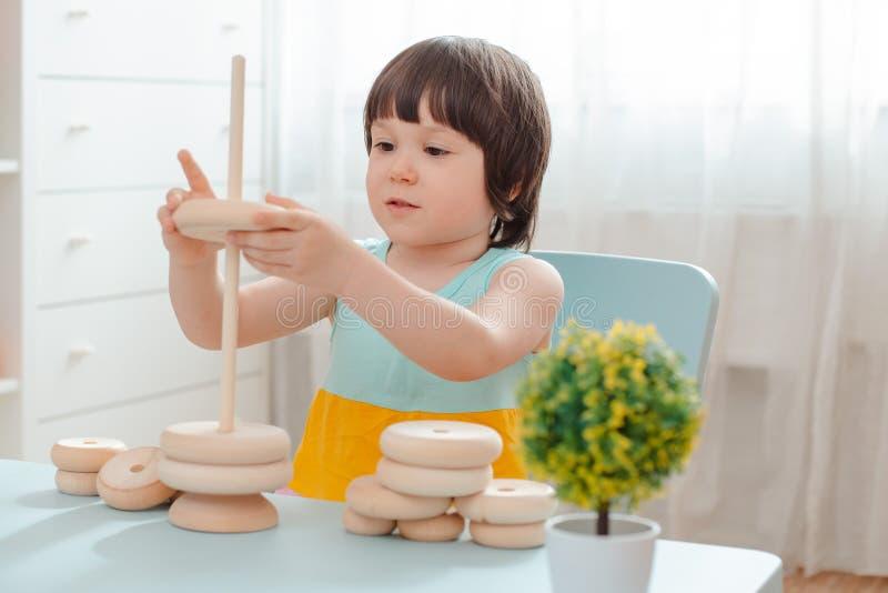 La niña recoge una pirámide sin pintar de madera Los juguetes de los niños de madera naturales seguros fotografía de archivo