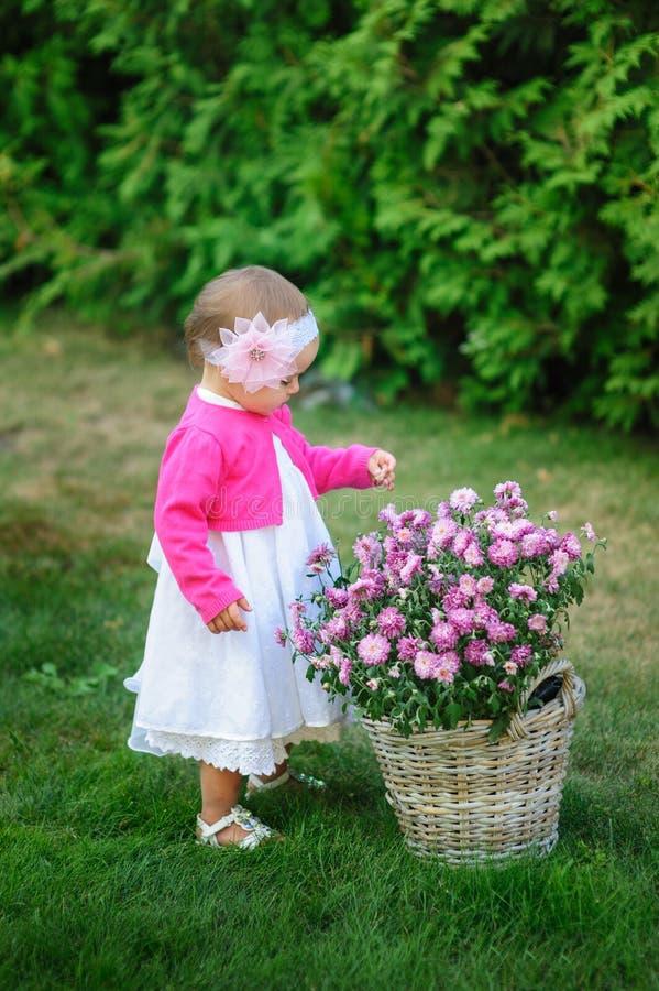 La niña se coloca cerca de una cesta de flores fotografía de archivo