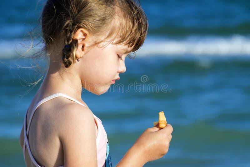 La niña se coloca con sus ojos abajo y sostiene una patata frita en su mano fotos de archivo