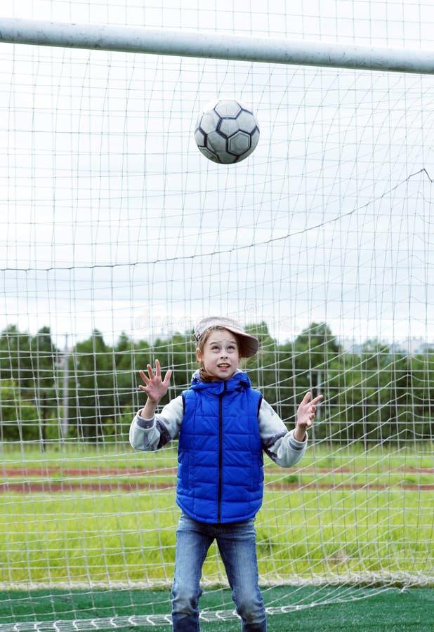 La niña se coloca en la puerta del fútbol como portero y quiere coger la bola imagenes de archivo