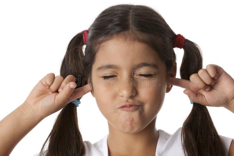 La niña se está cerrando los oídos con sus dedos fotos de archivo