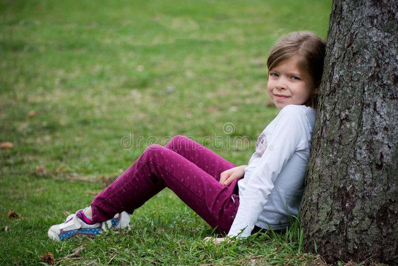 La niña se está sentando cerca del árbol en prado fotos de archivo libres de regalías