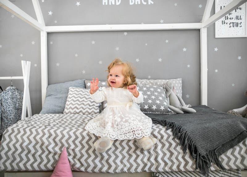 La niña se está sentando en la cama con su juguete imagenes de archivo