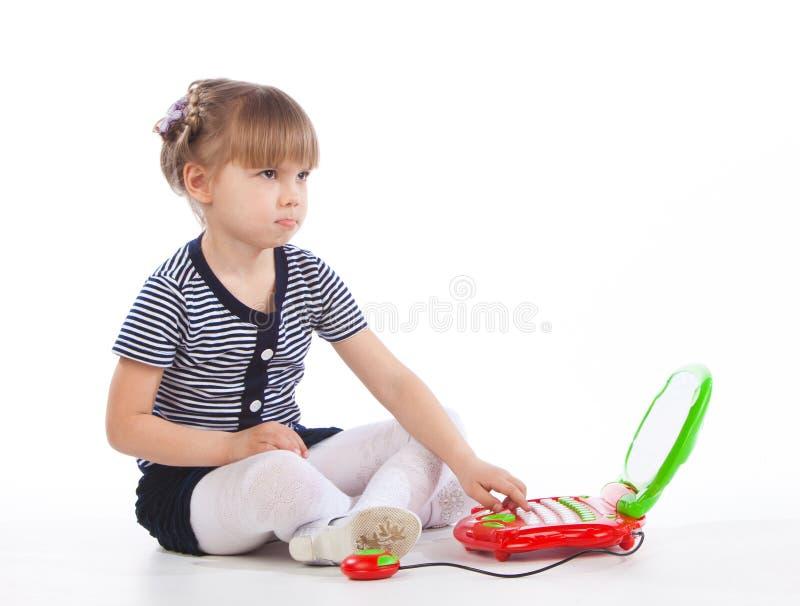 La niña se está sentando en el piso con el ordenador portátil y la mirada del juguete foto de archivo