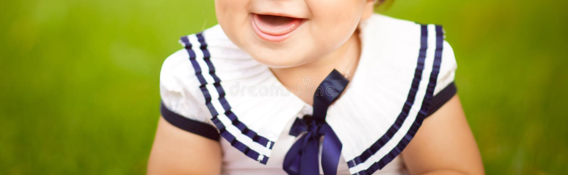 La niña se está sentando en la hierba verde en el jardín y la risa foto de archivo