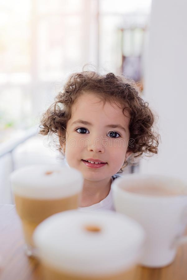 La niña se está sentando en las tazas del whith de la tabla de café y de cappucino, verticales fotografía de archivo libre de regalías