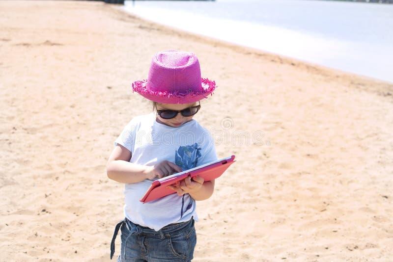 La niña se está sentando en la playa con una tableta en manos Día soleado y arena en la playa Muchacha en un sombrero rosado y imágenes de archivo libres de regalías