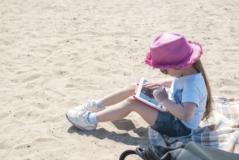 La niña se está sentando en la playa con una tableta en manos Día soleado y arena en la playa Muchacha en un sombrero rosado y fotografía de archivo