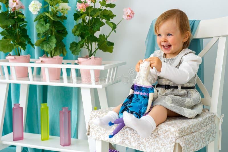 La niña se está sentando en una silla y una sonrisa grandes imagenes de archivo
