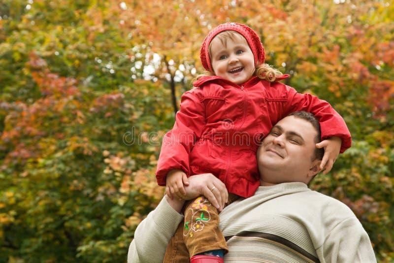 La niña se sienta en hombro en el hombre en parque fotos de archivo libres de regalías