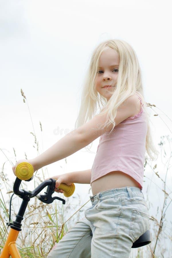 La niña se sienta en la bicicleta foto de archivo libre de regalías