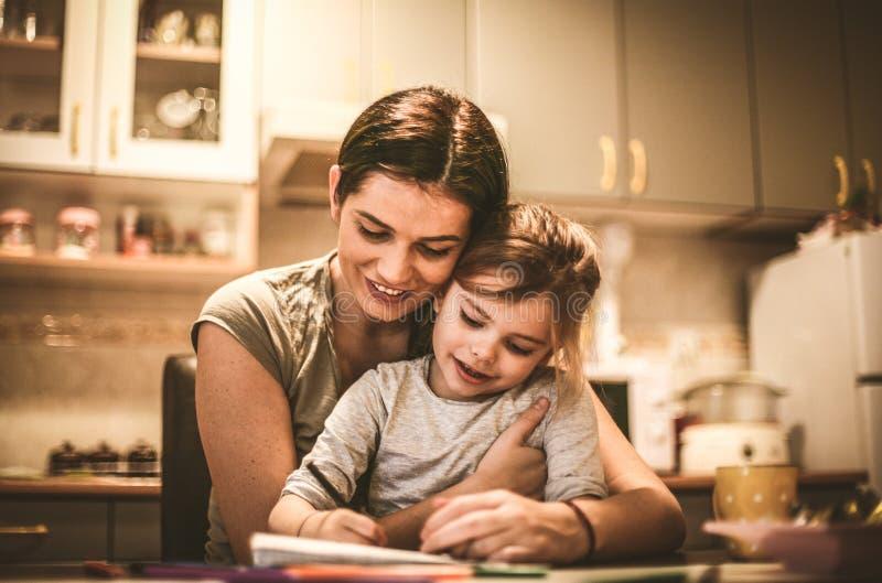 La niña se sienta en revestimiento y el dibujo de las madres fotografía de archivo libre de regalías
