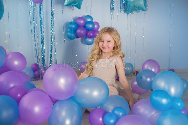 La niña se sienta en un piso de un estudio con muchos globos del color imagen de archivo libre de regalías
