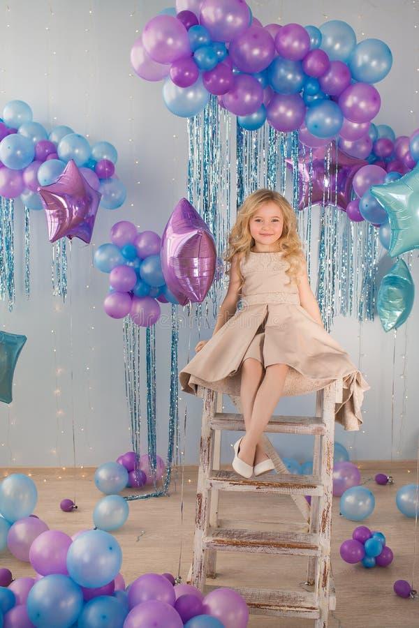 La niña sienta en las escaleras en un estudio con muchos globos del color foto de archivo libre de regalías