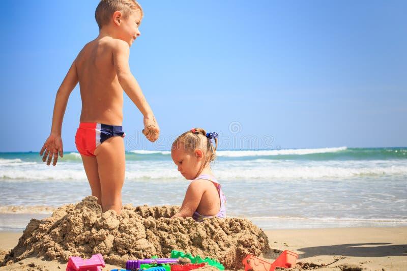 La niña sienta soportes del muchacho en montón de la arena en la resaca de la onda en la playa fotografía de archivo