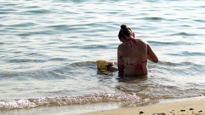 La niña sola juega solamente en agua poco profunda del mar foto de archivo libre de regalías
