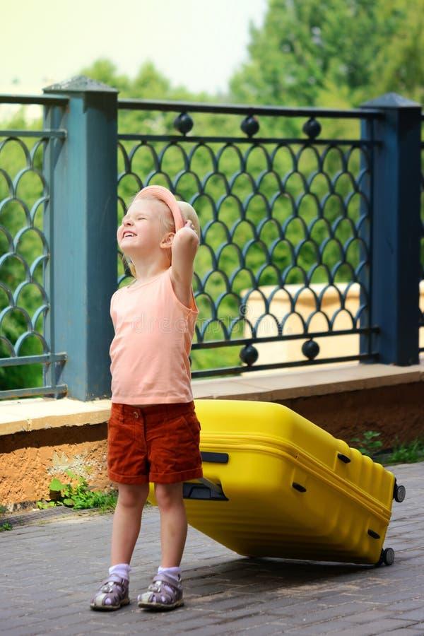 La niña sonríe y frunce el ceño en el sol Un niño en un sombrero y pantalones cortos rojos está llevando una maleta amarilla gran imágenes de archivo libres de regalías