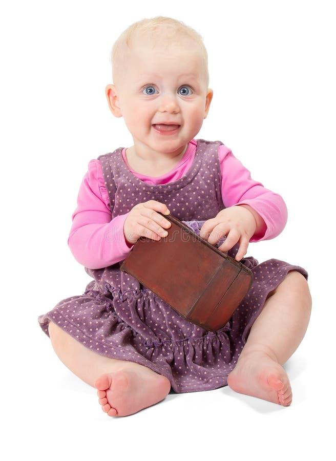 La niña sonriente feliz en el vestido violeta se sienta fotografía de archivo libre de regalías