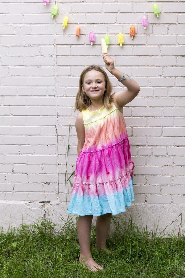 La niña sonriente que se colocaba con el brazo aumentó sostener un polo foto de archivo