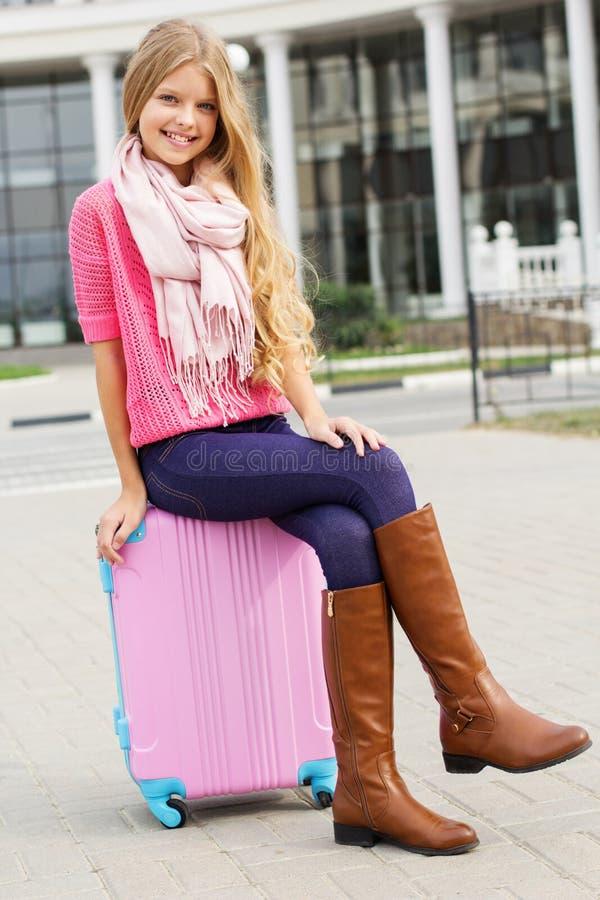 La niña sonriente se está sentando en bolso rosado del viaje imagenes de archivo