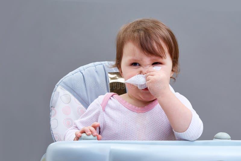 La niña sopla su nariz en un pañuelo de papel en fondo gris imagen de archivo libre de regalías