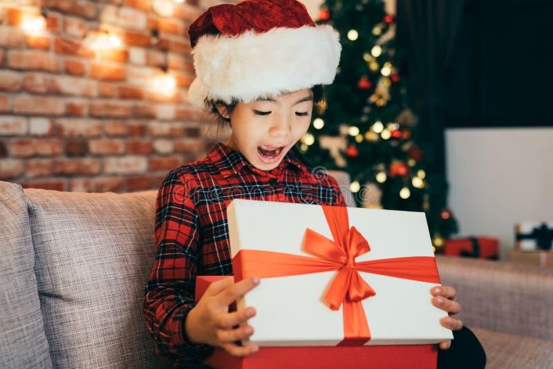 La niña sorprendió el regalo abierto de la Navidad en casa imagenes de archivo