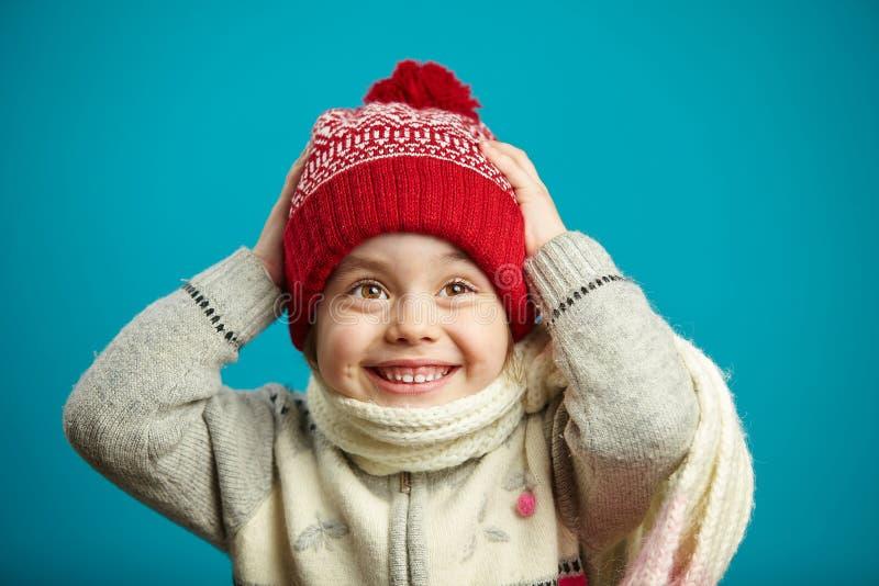 La niña sorprendida en sombrero rojo del invierno con una capilla y una bufanda, puso sus manos en la cabeza, expresa un stunnmen imagenes de archivo