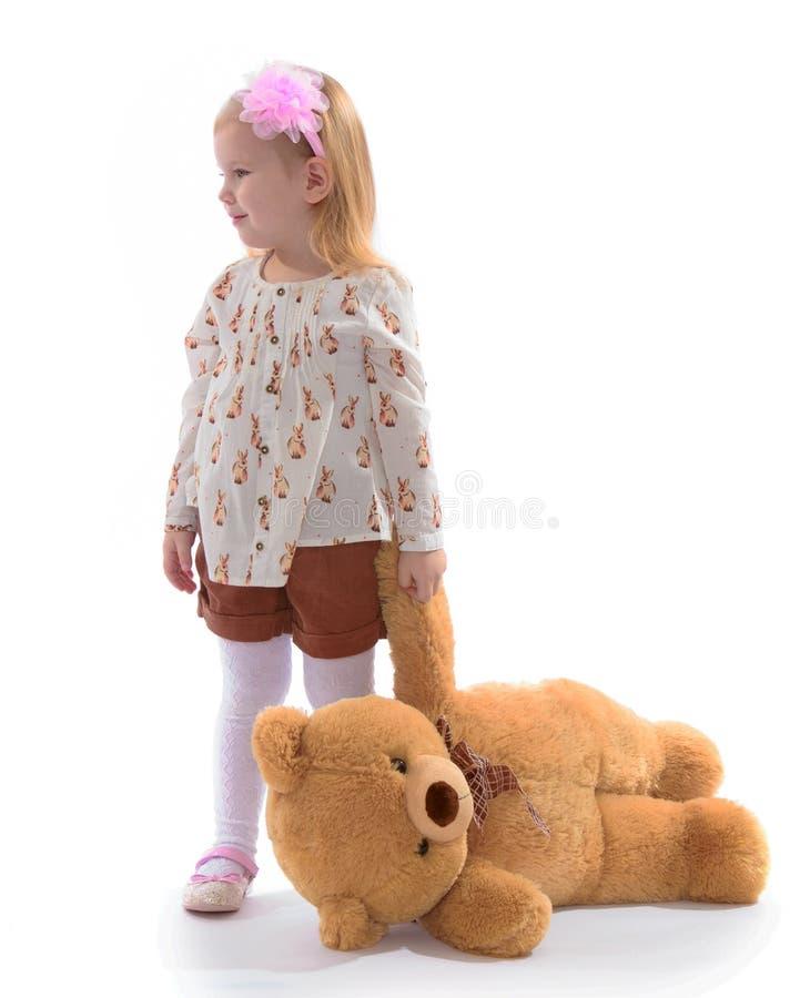 La niña sostiene la pata de un oso de peluche fotos de archivo libres de regalías